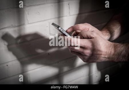 Un prisonnier en prison au moyen d'un téléphone mobile derrière les barreaux dans une cellule Banque D'Images