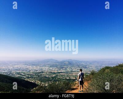 Vue arrière de l'homme debout sur la montagne contre Ciel Bleu clair