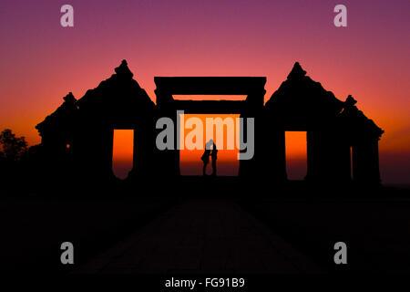 Silhouette Couple Kissing On Gateway de ruines Ratu Boko contre Ciel clair Banque D'Images