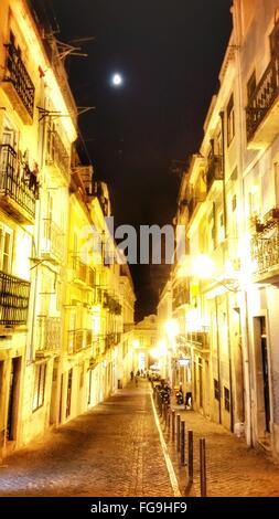 Rue Pavée au milieu d'édifices illuminés la nuit Banque D'Images