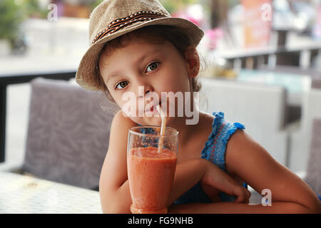 Fun kid cute girl drinking smoothie sain jus dans street restaurant. Closeup portrait Banque D'Images