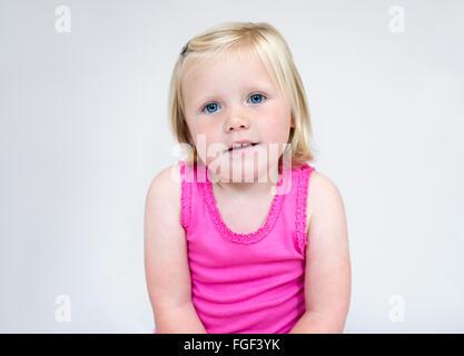 Portrait d'une jeune fille avec de courts cheveux blonds et aux yeux bleus portant un gilet rose smiling Banque D'Images
