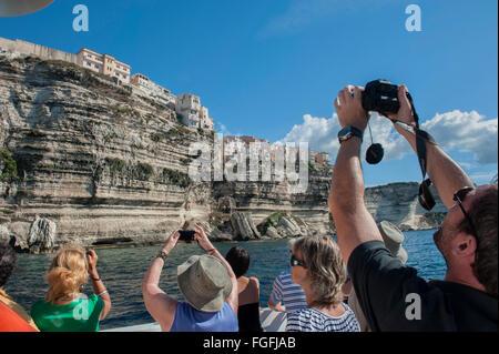 Les touristes armés de caméra à bord d'un bateau d'excursion guidée autour de Bonifacio. La corse. France Banque D'Images