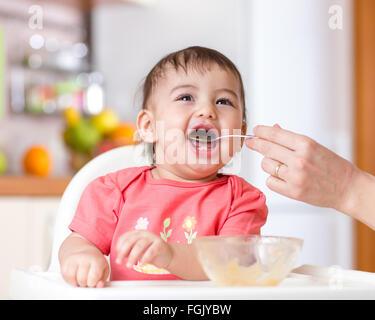 Smiling baby de manger des aliments sur la cuisine Banque D'Images