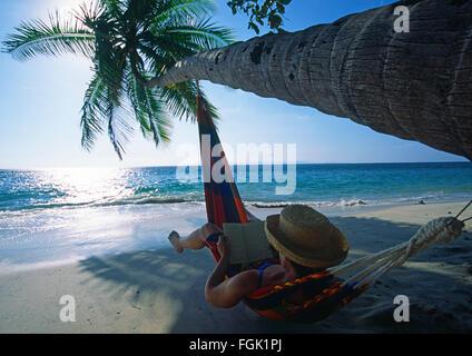 Une femme dans un hamac en lisant un livre sous un cocotier tree refoulées au fil de l'eau sur une plage sur la Banque D'Images