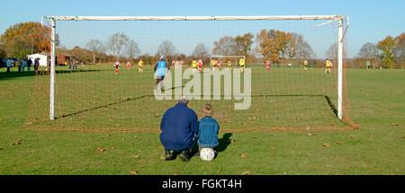 Père & Fils à balle derrière poteau de but regardant teen kids playing football match village jeu de soccer père vivre ensemble avec collage enfant UK