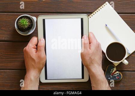 Tasse de café, et un bloc-notes électronique, sur un fond de bois, vue du dessus Banque D'Images
