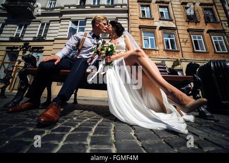 Mariée et le marié s'asseoir sur le banc Banque D'Images
