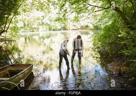 Père et fils avec des filets de pêche dans l'étang de la forêt Banque D'Images