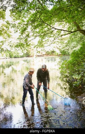 Père et fils avec des filets de pêche en étang Banque D'Images