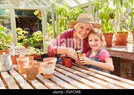 Portrait smiling grandmother and granddaughter potting plants in greenhouse Banque D'Images
