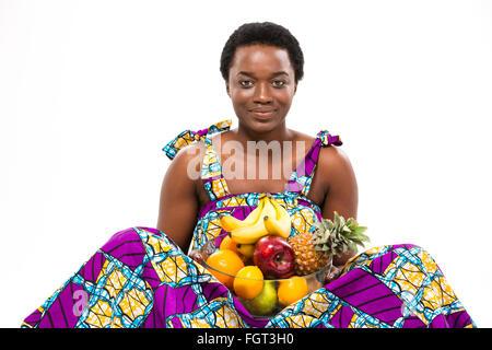 Cheerful belle jeune femme afro-américaine en robe d'assis et lumineux à maintenir les différentes fruits exotiques Banque D'Images