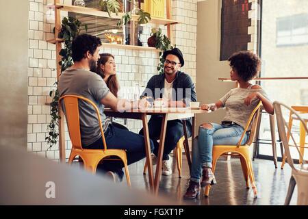 Les jeunes gens assis à une table de café. Groupe d'amis parler dans un café. Banque D'Images