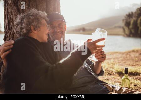 Portrait de relaxed mature couple assis à un arbre et le grillage du vin. Man woman drinking wine at camping o Banque D'Images