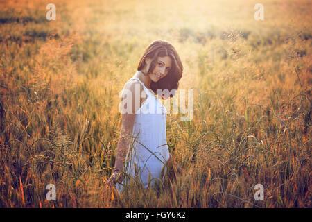 Belle jeune femme dans un champ d'été. Portrait de la lumière au coucher du soleil chaud Banque D'Images