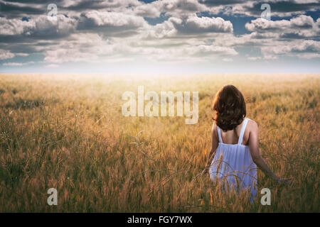 Femme regardant fixement un ciel dramatique dans un champ d'or . La lumière au coucher du soleil