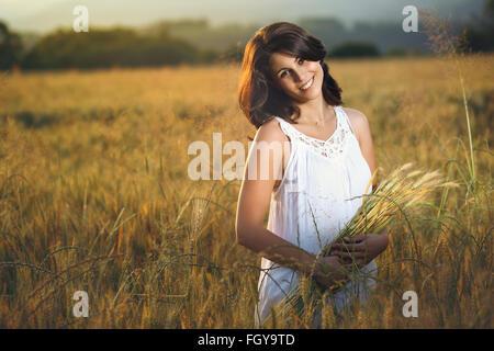 Belle femme dans un champ d'or au coucher du soleil. Portrait de la saison estivale Banque D'Images