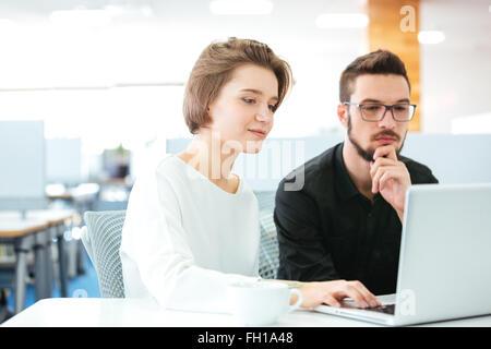 Jeune homme concentré et femme assise et de discuter de nouveau projet using laptop in office