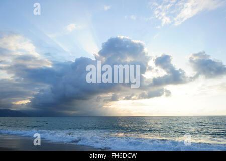 Nuages Sun Ray est allumé la lumière aux couleurs vives avec des vagues seascape or rolling au rivage comme sunbeam Banque D'Images