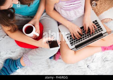 Vue de dessus de jeune femme et fille assise et à l'aide d'ordinateur portable et téléphone mobile écran vide à Banque D'Images