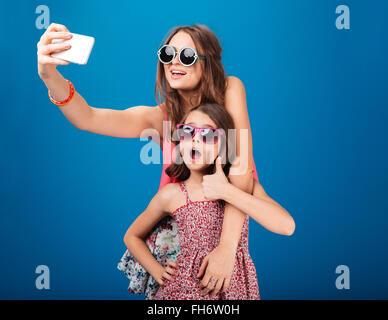 Deux charmantes sœurs heureux en prenant l'aide de lunettes selfies smartphone sur fond bleu Banque D'Images