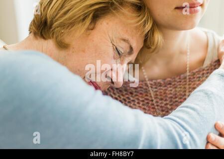 Senior woman with closed eyes appuyé contre l'épaule de la jeune femme Banque D'Images
