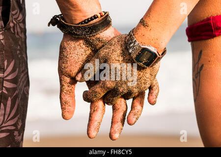 Close-up of couple holding hands de sable Banque D'Images