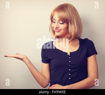Happy casual female model holding dans la main et présenter quelque chose de vide. Portrait vintage aux couleurs Banque D'Images