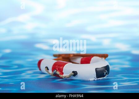 Caoutchouc jouet rouge et blanc voile avec palettes sur un papier bleu avec des vagues Banque D'Images