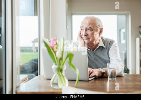 Portrait of smiling senior woman looking through window Banque D'Images