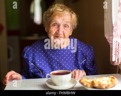 Une femme âgée assise dans la cuisine à boire le thé. Banque D'Images
