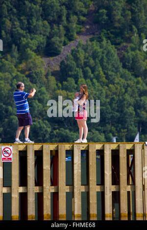 Parc National de Lake District. Man taking photo de sa femme et son bébé avec smart phone sur une jetée dans le Banque D'Images