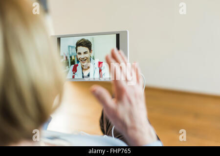 Senior woman looking at photo de jeune homme on digital tablet Banque D'Images