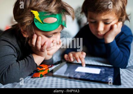 Deux petits garçons couchés sur un lit jouant avec digital tablet Banque D'Images