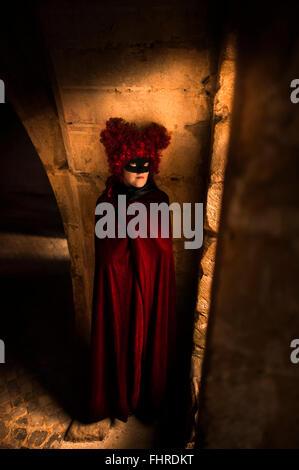 Figure féminine portant perruque rouge debout dans château par la fenêtre Banque D'Images