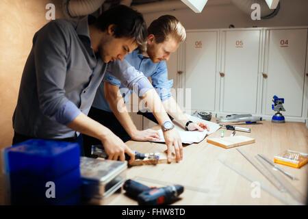 Deux designers qui travaillent ensemble en atelier avec des outils de précision Banque D'Images