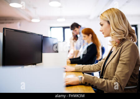 Businesswoman using computer in office while sitting at desk Banque D'Images