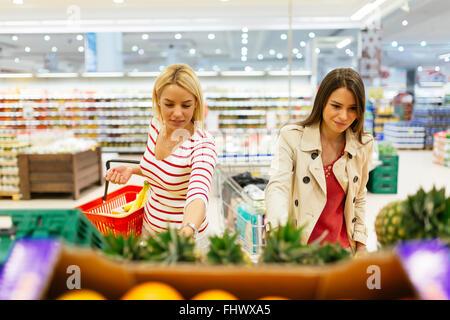 Belles femmes shopping fruits et légumes en supermarché Banque D'Images