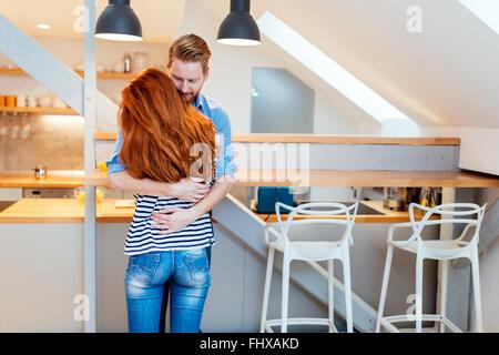 Beau couple heureux pour leur nouvelle maison et s'étreindre après déménagement dans Banque D'Images