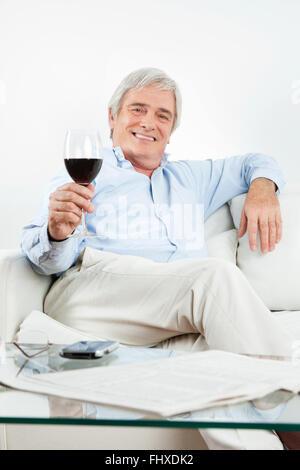 Happy senior man toasting avec verre de vin rouge Banque D'Images