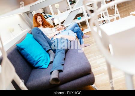 Couple cuddling dans bel intérieur salle de séjour tout en se trouvant sur canapé Banque D'Images