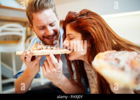 Le partage de deux ou trois pizzas et manger ensemble heureusement Banque D'Images