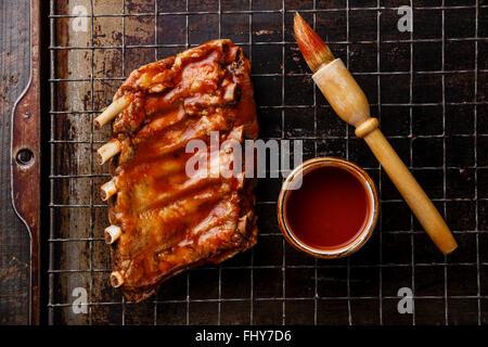 Côtes de porc fumé grillé au barbecue sauce et pinceau sur dark metal plaque historique Banque D'Images