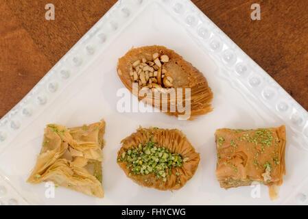Délicieux baklava couverts à la pistache et aux amandes, affichées sur une plaque blanche, pâtisserie traditionnelle Banque D'Images