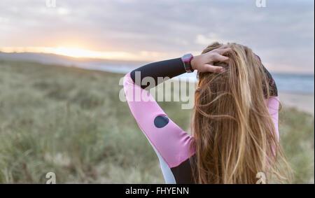 Jeune femme surfer sur la plage Banque D'Images