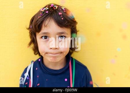 Little Boy pulling funny face en face de mur jaune tandis que les confettis tombant sur lui Banque D'Images