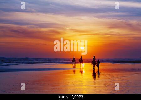 Silhouette noire de happy family cheval aventure sur la plage de la mer de sable sur le fond de ciel de coucher Banque D'Images