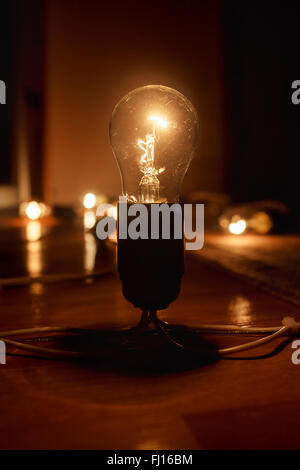 Grande lampe à incandescence électrique brossé sur le sol, sur un fond sombre. La lumière dans l'obscurité. Banque D'Images