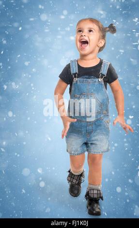 Jolie petite fille heureuse de jouer contre fond bleu avec abstract snow Banque D'Images