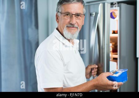 Man dans sa cuisine par le réfrigérateur (tons de couleur peu profondes; image DOF) Banque D'Images